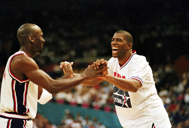 Magic Johnson greets teammate Michael Jordan as Jordan takes the bench during a U.S. game in the Basketball Tourney of the Americas game in Portland on July 12, 1992. Johnson, who withdrew from competition in the NBA earlier after testing positive for the HIV virus, is playing the game with all of the skill and heart he showed in the NBA. (AP Photo/Jack Smith)